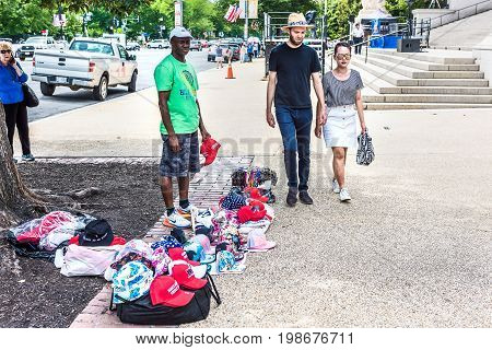 Washington DC USA - July 3 2017: Man selling souvenirs and President Trump's red Make America Great Again hats on sidewalk street