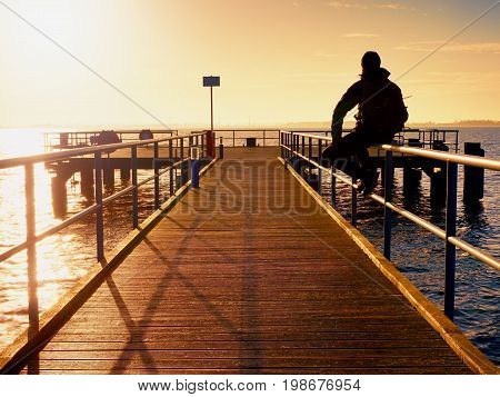 Alone Man Goes On The Wooden Pier In The Sunrise