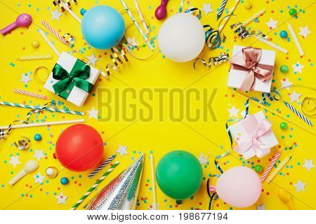 Birthday party background or frame with colorful balloon gift confetti silver star carnival cap candy and streamer. Flat lay style. Holiday flyer with copy space.