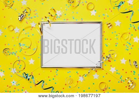 Party carnival or birthday background decorated silver frame with colorful confetti and streamer on yellow table top view. Flat lay style. Holiday mockup. Greeting card with copy space.