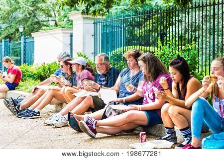 Washington DC USA - July 3 2017: People sitting eating fast food on sidewalk from food trucks on street by National Mall on Independence Avenue