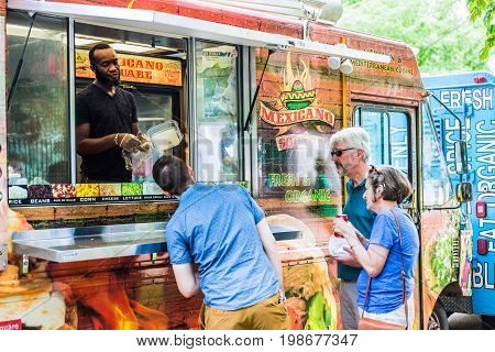 Washington DC USA - July 3 2017: Food trucks on street by National Mall with Mexican food storefront on Independence Avenue and people buying