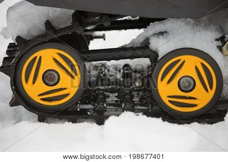 Rollers yellow and black caterpillars of the snowmobile with the snow and water. Close-up drops parts tires winter