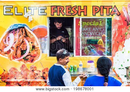 Washington DC USA - July 3 2017: Food trucks on street by Elite Fresh Pita storefront on Independence Avenue and people buying