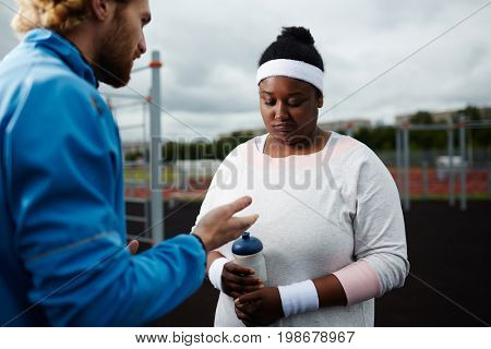 Personal trainer motivating plump woman