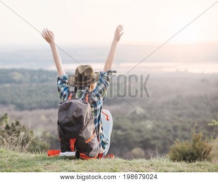 Backpacker woman enjoy life, arms raised and cheer to sunrise or sunset. Lifestyle concept.