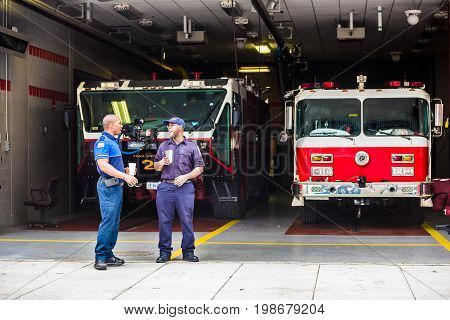 Washington DC USA - July 3 2017: Happy firefighters firemen smiling in downtown by trucks at fire station