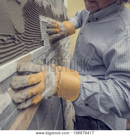 Closeup of manual worker in protection gloves pushing the tile into the cement on the wall while tiling a wall with ornamental tiles retro effect faded look.