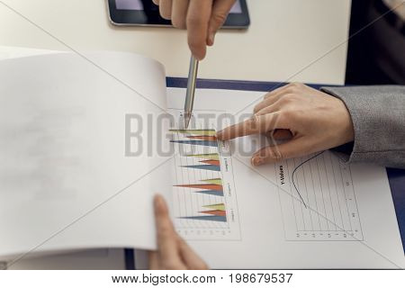 Two Business Partners Pointing At The Business Graph Representation