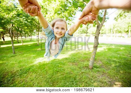 Hands of parent holding little girl and whirling her in park