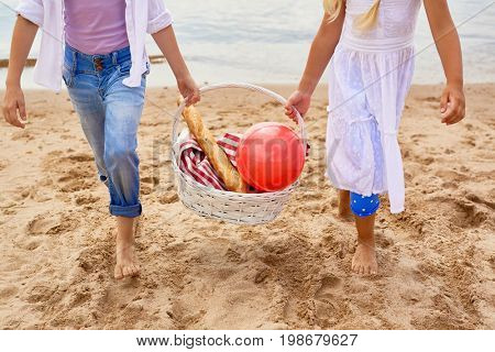 Little friendly girls carrying basket with tablecloth, red ball and crusty baguette while walking down sandy beach