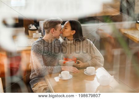 Girlfriend kissing her sweetheart on nose to express thanks for present
