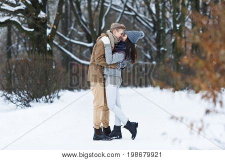 Embracing couple flirting in wintery park at dating