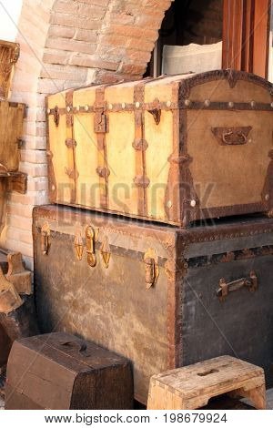 Two vintage wooden chests upholstered in fabric with decorative wood and metal details