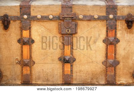 Vintage wooden chest upholstered in fabric with decorative wooden and metal details. Close-up photo