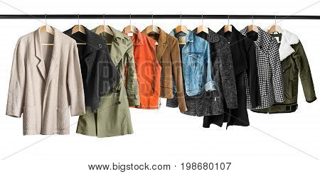 Group of coats and jackets hanging on clothes racks isolated over white