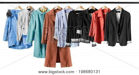 Group of jackets and coats hanging on clothes racks on white background