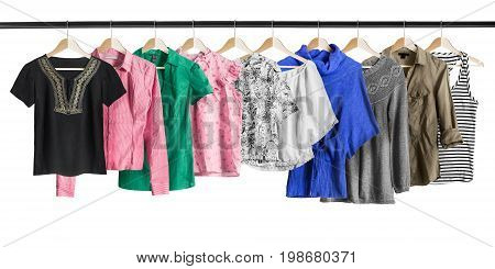 Group of shirts and pullovers hanging on clothes racks isolated over white