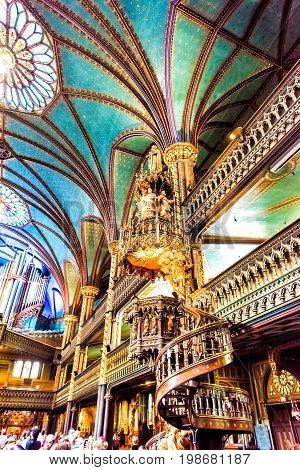 Montreal Canada - May 28 2017: Inside Notre Dame Basilica during mass with many people taking pictures of detailed architecture