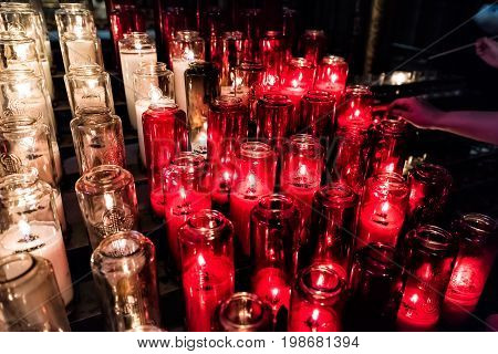 Red And White Votive Candles With Yellow Flame In Church With Hand Lighting Them