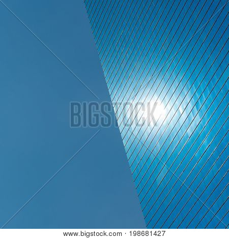 Blue architecture background. The left side is blue sky, the right half is a modern blue glass office building with a spot that is reflection of the sun. Fine for placing text or logo in the center