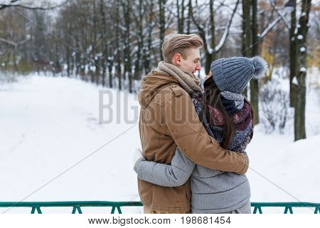 Young amorous guy and girl embracing in park