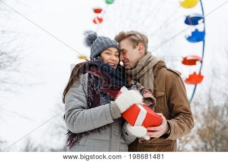 Laughing girl taking giftbox from her boyfriend in amusement park on wintery day
