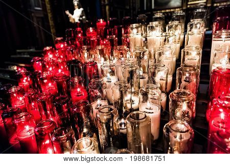 Red And White Votive Candles With Yellow Flame In Church