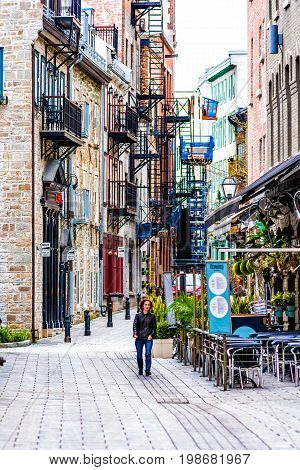 Montreal Canada - May 28 2017: Old town area with person walking in cobblestone alley during summer day in Quebec region city