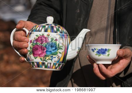 Kettle and a bowl in his hands. Tajik porcelain teapot and bowl in hands. Traditional national custom treats tea in Central Asia. Tajikistan