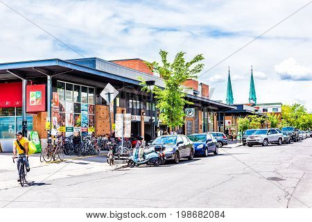 Montreal Canada - May 28 2017: Jean Talon farmers market building exterior with people cars and garage parking entrance