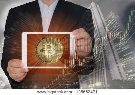 Blockchain concept : Rise of Bitcoin price. Business man holding tablet showing bitcoin on screen with increasing price graph and buildings in background. Multiple exposure technique.