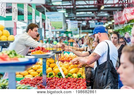 Montreal Canada - May 28 2017: People trying samples and buying produce by fruit and vegetable stands at Jean-Talon farmers market with coin change