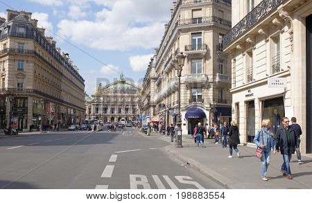 ParisFrance- April 29 2017: Scenic view of the Avenue de l Opera in Paris with the Comedie Francaise theater in the foreground and the Palais Garnier opera in the background. On the street pedestrians and moving vehicles