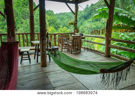 Green and red sleeping cot in a bamboo hut