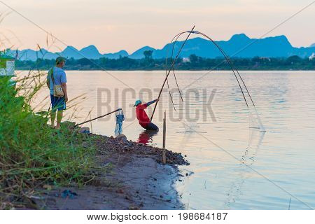 Nakhon Phanom, Thailand - May 11, 2017: Fisherman (unidentified) fishes with a net on Mekong river in sunset time. This is Thakhek area, Laos on the opposite side of the river