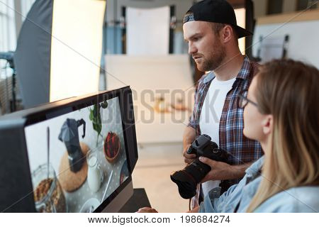 Photographer and designer discussing one of shots on monitor display while choosing best ones