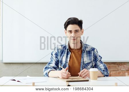 Teenage scholar sitting by desk and drawing pictures with pencil