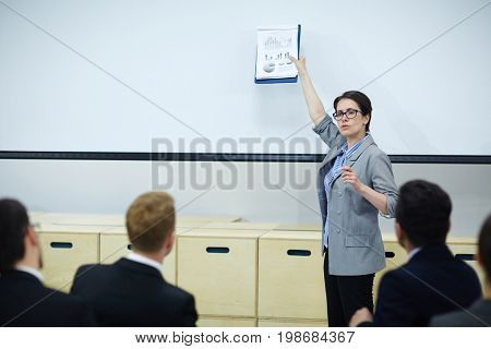 Professional economist or banker making report on whiteboard for group of young specialists