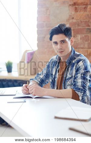 Young learner sitting by desk in classroom of contemporary college