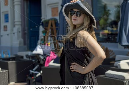 A young girl in a black hat with fields and white coturas and a black short mini dress with strasses posing on the pantone (landing stage) of the Volga River. Russia.