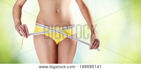 woman holding meter with hands near waistline isolated on blurred green background body care diet concept