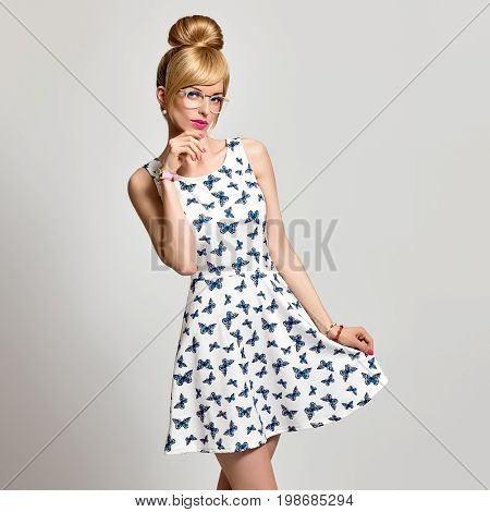 Fashion Beauty Sensual Blond Girl in Stylish glasses, Summer Outfit. Funny Mood. Stylish Trendy Pinup hairstyle, fashion Makeup, Blue Eyes. Glamour Romantic Model in Butterfly summer Dress