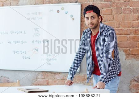 Young learner in casualwear leaning against desk by whiteboard in classroom