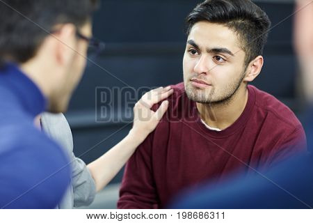 Sad man listening to advice of colleague during group session