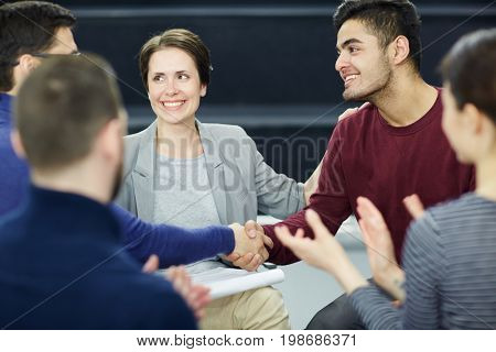 Psychological group attendants handshaking after talk while their colleagues applauding