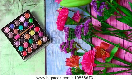 Colorful makeup palette and beautiful flowers on multicolored wooden background