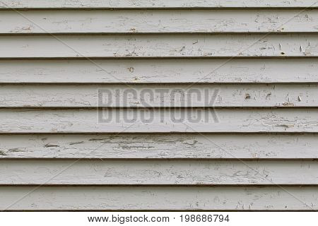 Peeling white clapboards on a wood house background