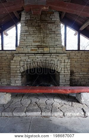 Picnickers may sit on a bench in front of the fireplace in the historic Shorewood Grove Shelter, in the Hammel Woods Forest Preserve in Shorewood, Illinois.