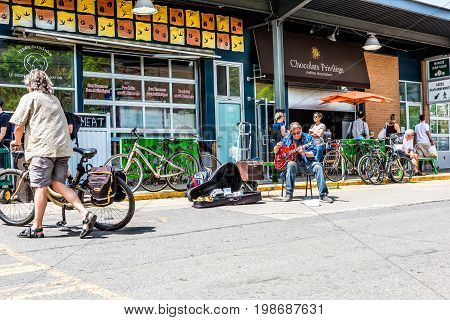 Montreal Canada - May 28 2017: Man playing guitar by produce vegetable stands outside Jean-Talon farmers market with people on bikes looking during bright sunny day